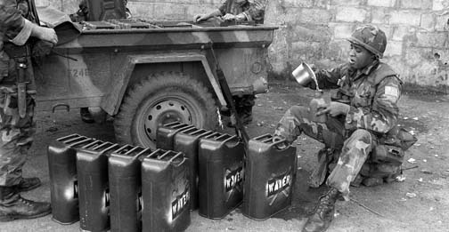 Marines replenish their water supplies as they participate in Operation URGENT FURY.
